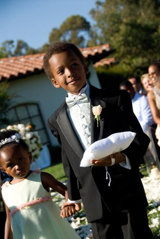 ring-bearer-in-tux-holds-pillow-and-hand-of-flower-girl