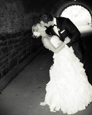 black-and-white-photo-of-groom-dipping-bride-in-tunnel