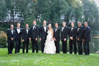bride-and-groom-with-tux-groomsmen-in-front-of-lake