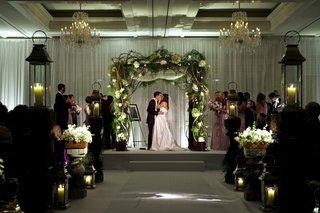 bride-and-groom-kissing-under-rustic-chuppah