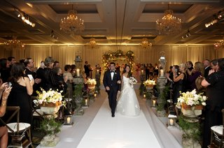 couple-walking-up-pedestal-lined-aisle