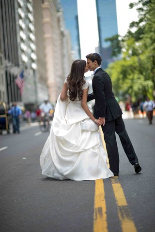 bride-in-a-monique-lhuillier-gown-with-a-pick-up-skirt-kisses-groom-in-a-black-tuxedo-on-the-street