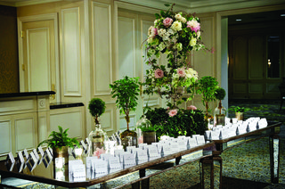 seating-cards-on-long-mirror-table-with-tall-flowers