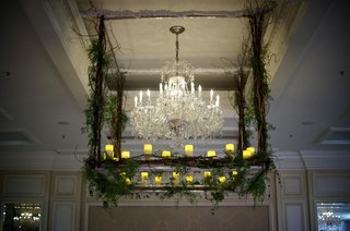 crystal-chandelier-surrounded-by-branch-and-greenery
