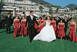 bridesmaids-wearing-red-dresses-walk-with-groomsmen-and-newlyweds