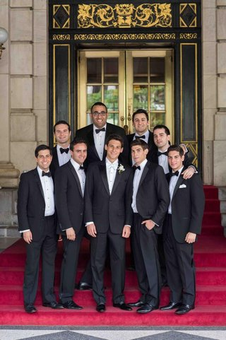 groom-and-groomsmen-in-black-tuxedos-and-bow-ties-in-front-of-the-plaza