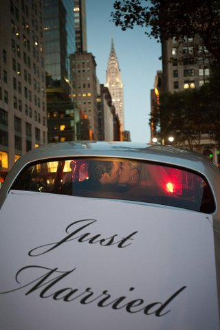 bride-and-groom-kiss-in-back-of-car-in-front-of-chrysler-building