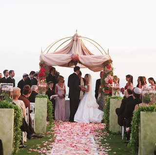 pink-and-red-roses-petals-cover-aisle-leading-to-chuppah