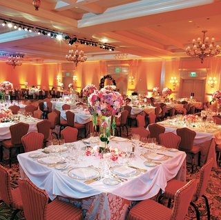 ballroom-with-white-tables-red-chairs-and-pink-flowers