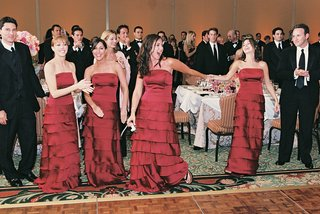 bridesmaids-wearing-red-dresses-sing-at-reception