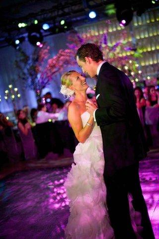 bride-and-groom-dance-on-purple-dance-floor-at-indoor-reception