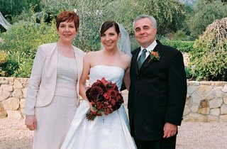 parents-stand-with-bride-holding-red-flower-bouquet