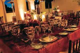 wedding-decorations-fit-for-a-king-with-red-tablecloths-and-gold-rimmed-crystal