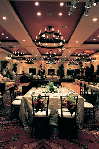 amber-ballroom-with-white-tables-and-red-and-green-floral-centerpieces
