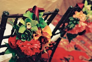 bundles-of-red-yellow-and-green-flowers-tied-to-chair-backs-with-red-ribbon