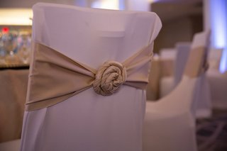 wedding-reception-with-chairs-in-white-sleeves-and-golden-fabric-rosette