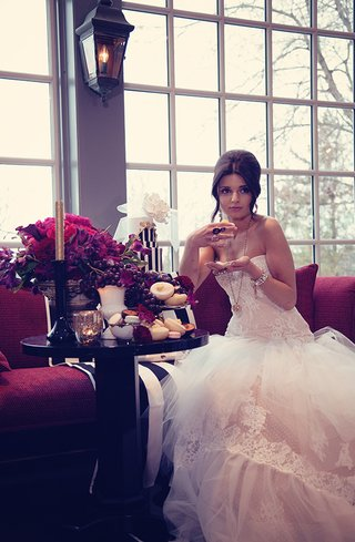 bride-in-a-strapless-lace-and-tulle-gown-with-various-golden-rings-on-each-hand-eating-cake