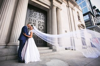 couple-in-front-of-vibiana-in-downtown-los-angeles-long-cathedral-veil-at-a-former-cathedral