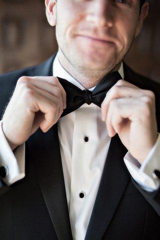 groom-fixing-his-bowtie-black-white-tuxedo-smirk-wedding