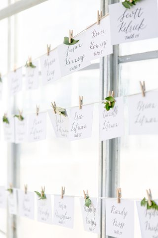 wedding-reception-twine-with-esocrt-cards-leaves-miniature-clothespins-on-line-greenhouse