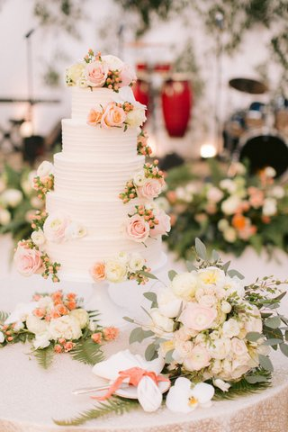 wedding-cake-with-fresh-flowers-pink-peach-white-roses-ranunculus-flowers-texture-pattern-linen