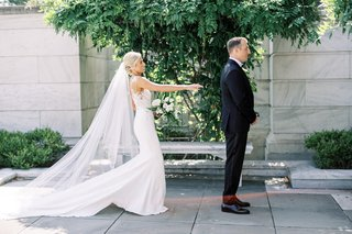 bride-in-form-fitting-pronovias-wedding-dress-cathedral-veil-first-look-with-groom-tuxedo