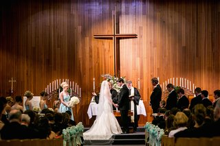 bride-and-groom-in-large-church-in-front-of-cross
