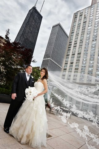 bride-and-groom-stand-in-chicago-brides-vera-wang-veil-flowing-in-the-wind-white-orchid-bouquet