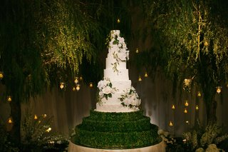 wedding-cake-white-with-flowers-and-greenery-hedge-boxwood-trees-candle-lights-forest