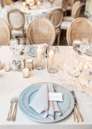 wedding-reception-place-setting-light-blue-charger-plate-grey-napkin-place-card-candles-cane-chair
