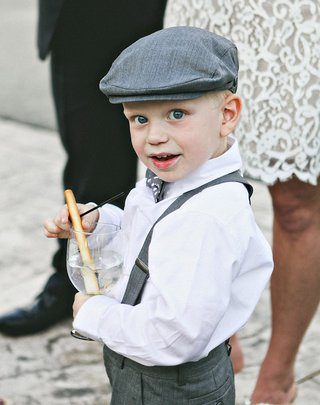 ring-bearer-in-button-down-grey-suspenders-pants-newsboy-cap-and-polka-dot-bow-tie-holds-glass