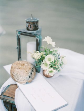 white-guest-book-with-rose-gold-calligraphy-with-driftwood-small-floral-arrangement-antique-lantern