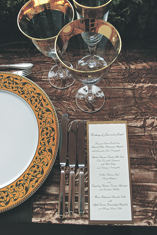 reception-place-setting-with-a-golden-bordered-plate-and-glasses-and-menu-with-script-font