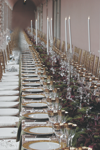 long-reception-table-topped-with-gold-rimmed-china-and-glassware-runner-of-flowers-and-candelabra