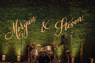 wedding-reception-calligraphy-cutout-signs-on-green-hedge-wall-behind-live-band-stage