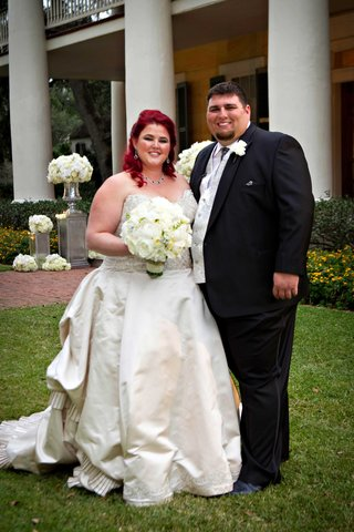 bride-in-strapless-eve-of-milady-ball-gown-with-bright-red-hair-and-groom-in-tuxedo-with-silver-vest