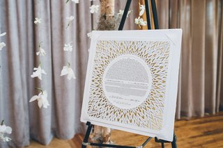floating-flowers-on-strings-with-birch-branches-ketubah-on-stand-gold-details-circle-sunburst-design
