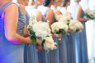 bridesmaids-in-blue-dresses-at-ceremony-holding-flowers