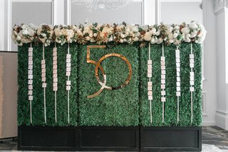 green-hedge-wall-with-escort-cards-and-gold-interlocking-number-for-50th-anniversary