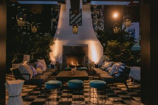 wedding-reception-lounge-area-lanterns-overhead-checkerboard-floor-fireplace-ottoman-velvet
