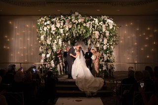 bride-and-groom-kiss-on-stage-wedding-ceremony-white-orchid-greenery-blush-flowers-jewish-wedding