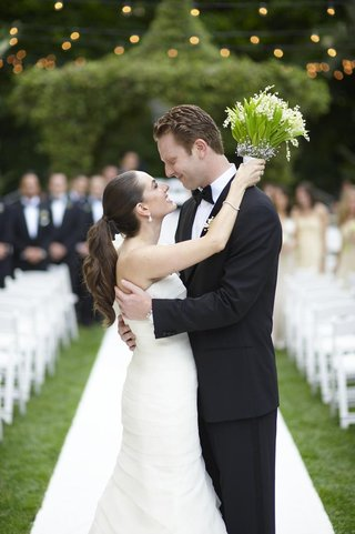 newlyweds-embracing-on-outdoor-wedding-aisle