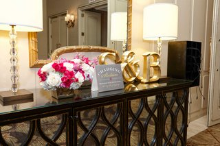 phone-charging-station-with-monogram-letter-initials-and-pink-white-flowers-ballroom-reception