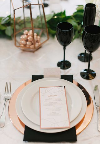 a-tablescape-featuring-black-white-and-copper-accents-in-chargers-glasses-linens-and-green-runner