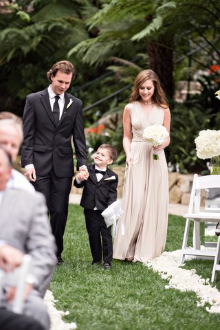 ring-bearer-holds-hands-with-groomsman-in-kenneth-cole-and-bridesmaid-in-tan-bhldn-dress