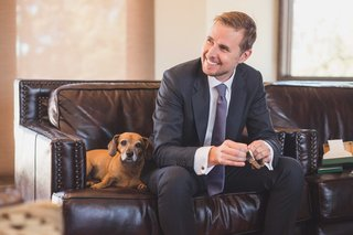 groom-smiling-with-dachshund-beagle-doxle-mix-dog-on-leather-sofa-in-grooms-suite