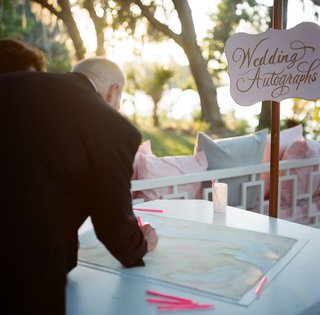 wedding-guests-signing-custom-map-with-pink