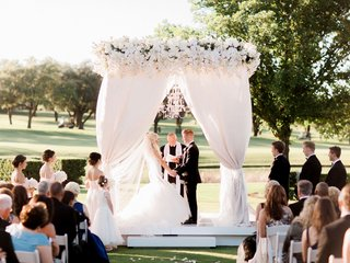 bride-in-wedding-dress-black-tux-on-groom-chandelier-outdoor-wedding-ceremony-all-white-decor-flower
