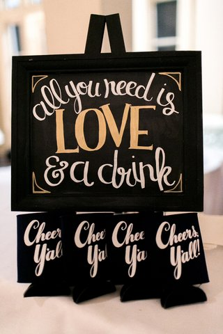 all-you-need-is-love-a-drink-sign-cheers-yall-black-koozies-at-wedding-reception