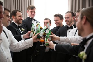a-groom-and-his-groomsmen-clad-in-black-tuxedos-toast-to-his-upcoming-marriage